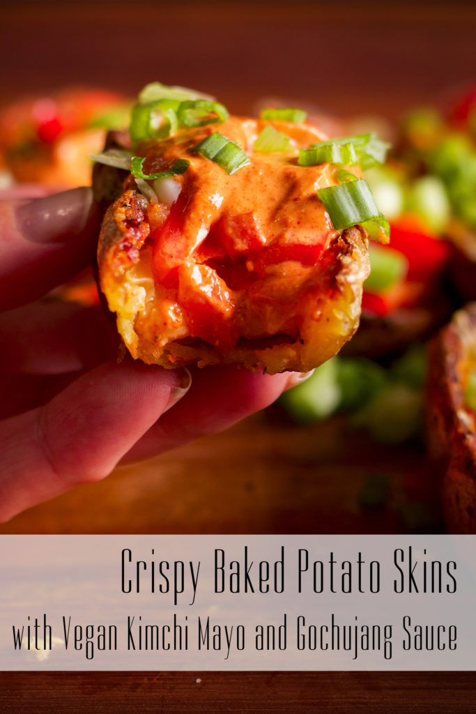 Someone holding up a baked potato skin with kimchi mayo and Gochujang sauce so you can see the cheesy inside.