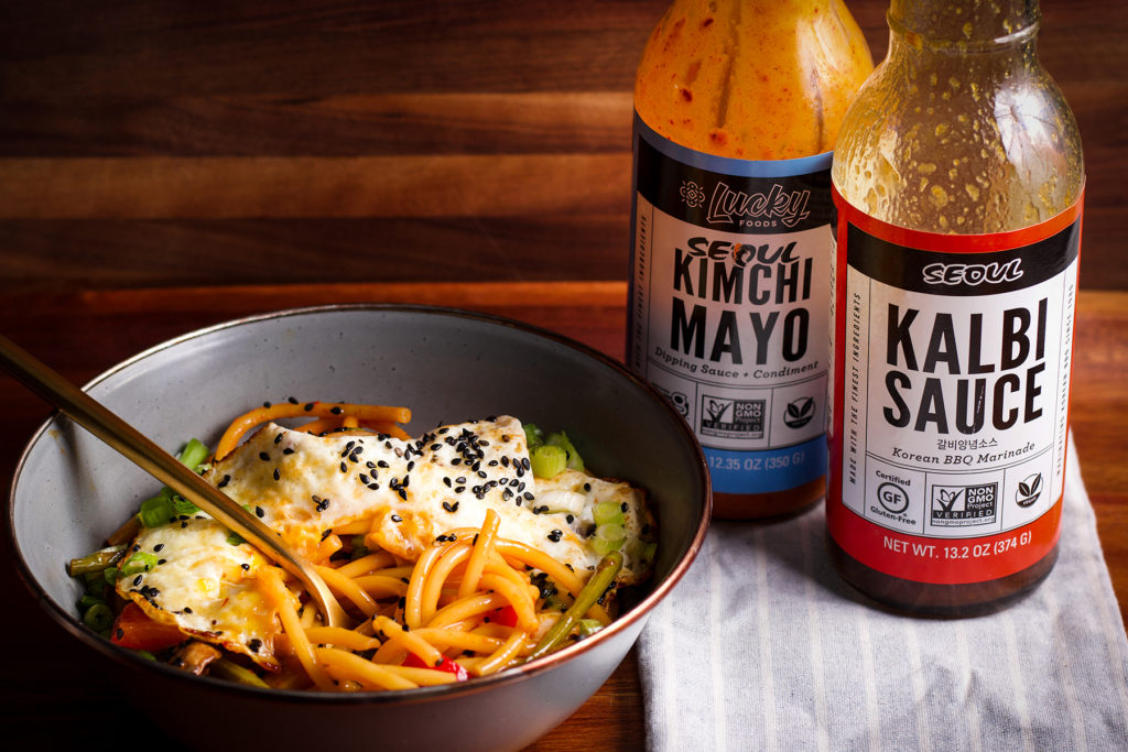 A bowl of Asian Noodles with Creamy Kimchi Sauce and a fried egg next to two bottles of Asian sauce.