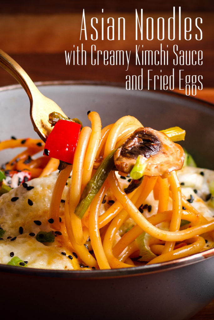 Someone using a gold fork to lift a bite of Asian Pasta with Creamy Kimchi Sauce with a fried egg.