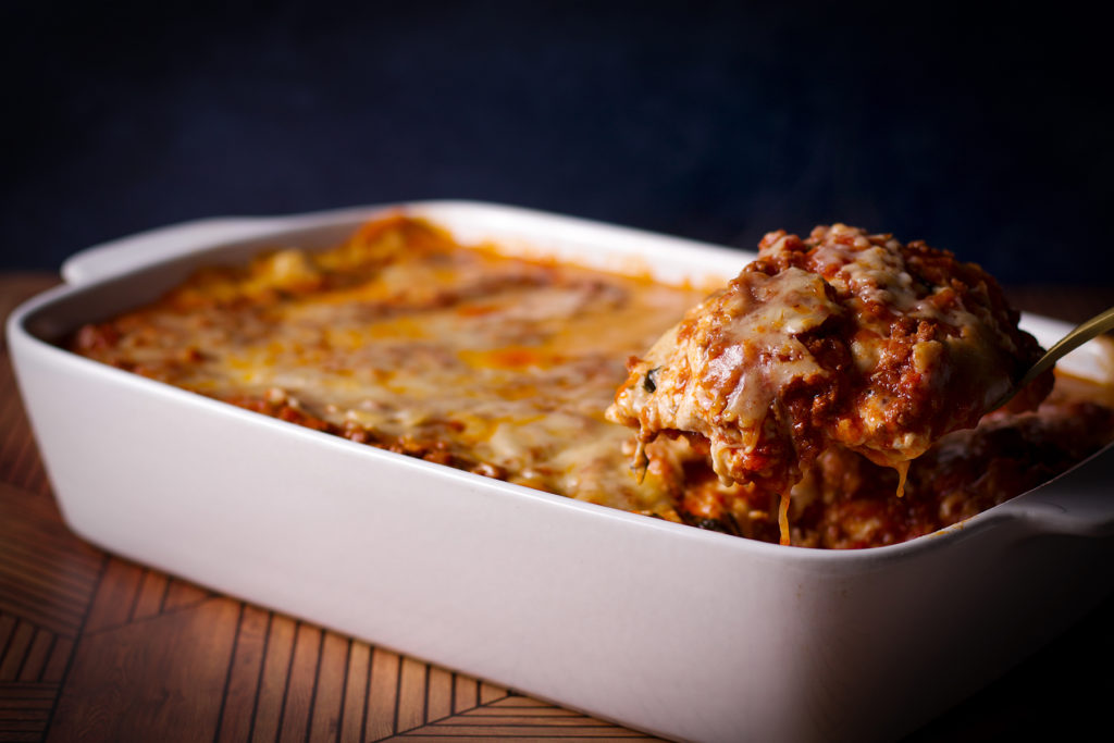 Someone using a spatula to serve a portion of lasagna bolognese from a white casserole dish.