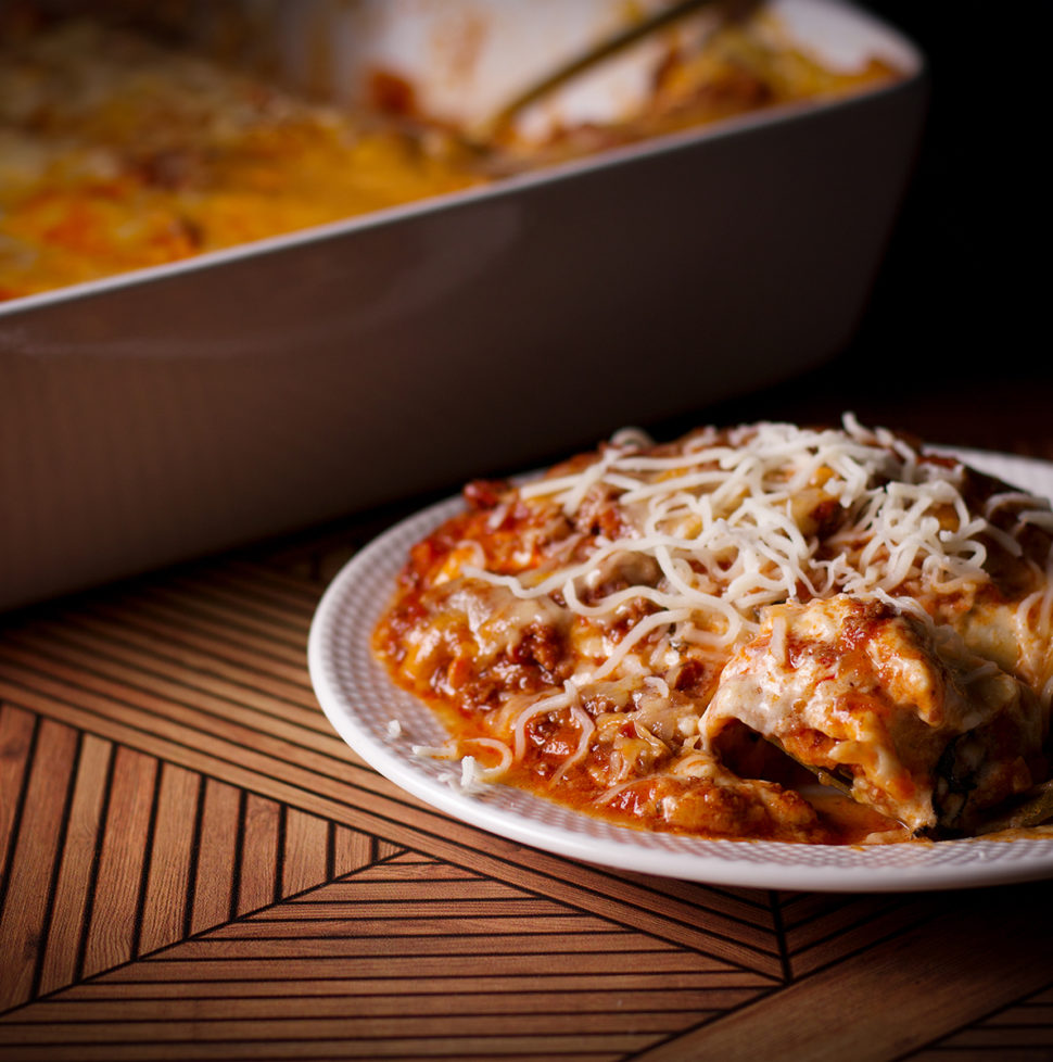 A plate of lasagna bolognese with the pan of lasagna in the background.