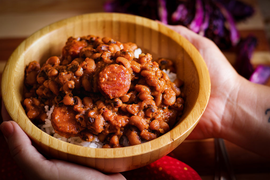 A bowl of Black Eyed Peas with Andouille Sausage served over rice.